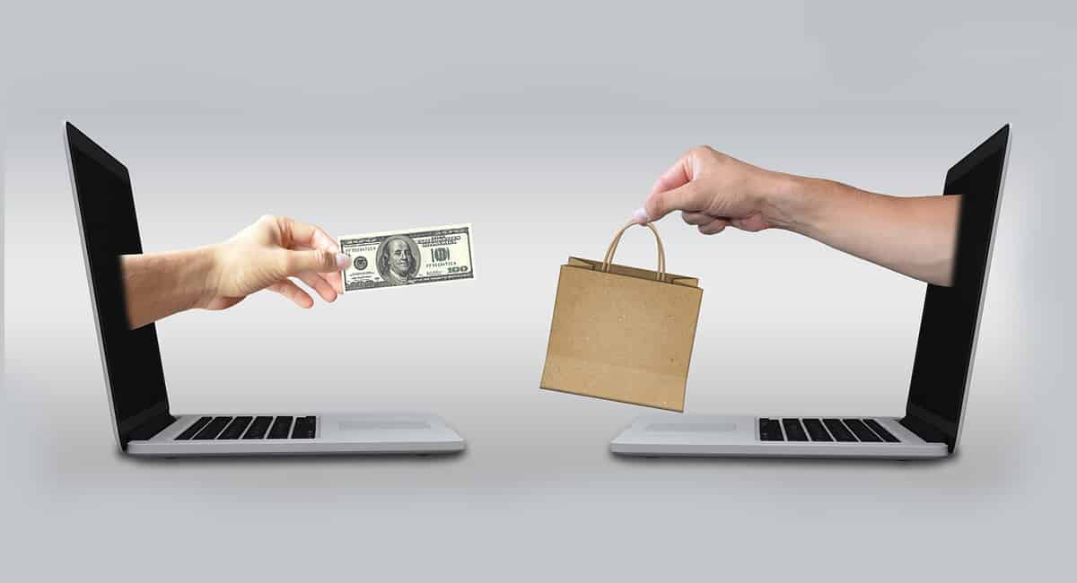 two hands coming out of screens exchanging money for goods in ecommerce
