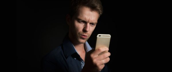 man with interested look engaged on mobile phone