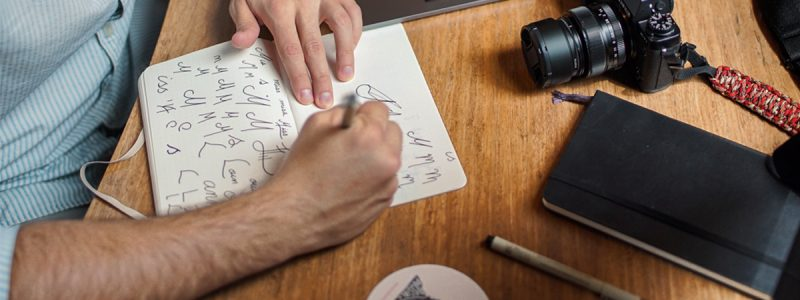 hands sketching corporate logo designs on paper with desktop and camera adjacent